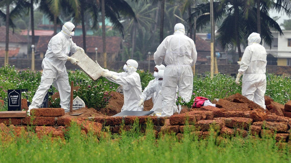 Doctors and relatives wearing protective gear dig a grave to bury the body of a victim, who lost his battle against the brain-damaging Nipah virus, in the southern Indian state of Kerala, India, May 24, 2018. (Reuters)