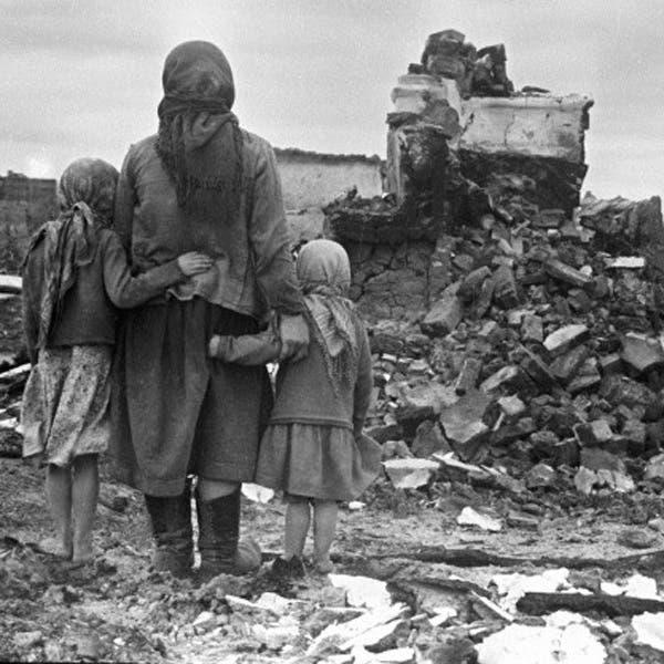 صورة لعدد من الناجين برجيف أثناء نظرهم للخراب الذي لحق ببيوتهم