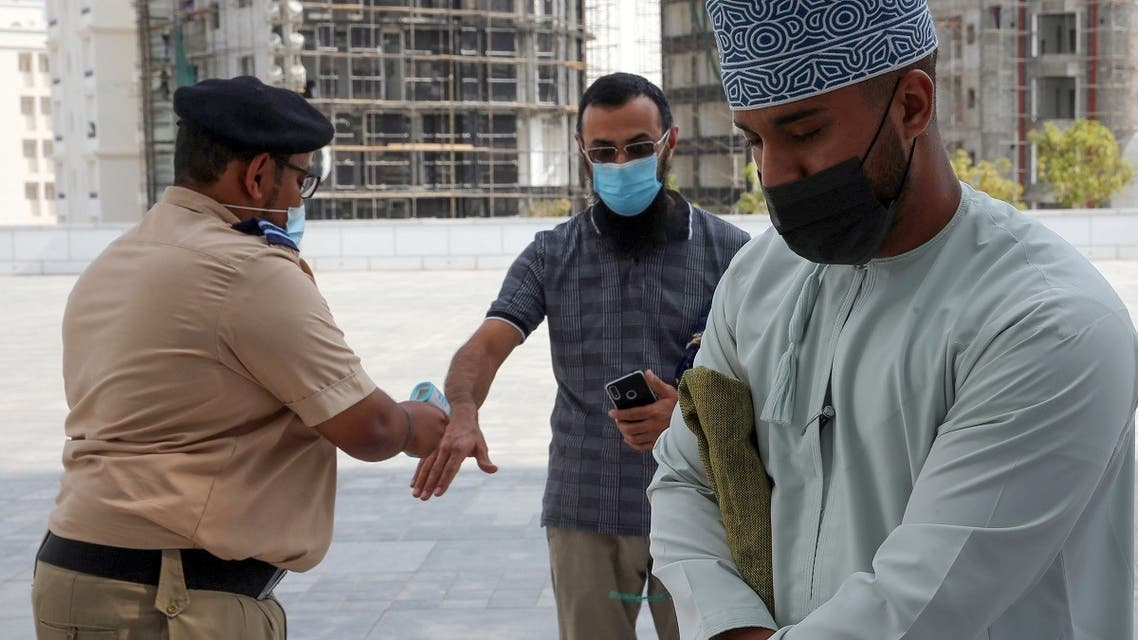 Mask-clad men use disinfecting gel and get their temperature checked before entering the Mohammed al-Amin Mosque in the Omani capital Muscat, November 15, 2020. (Mohammed Mahjoub/AFP)