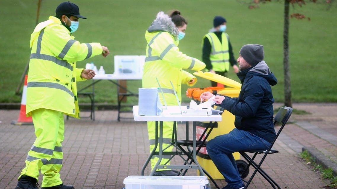 A health worker talks with a man taking a swab test in Goldsworth Park, as the South African variant of the novel coronavirus is reported in parts of Surrey, in Woking, Britain, on February 1, 2021. (Reuters)