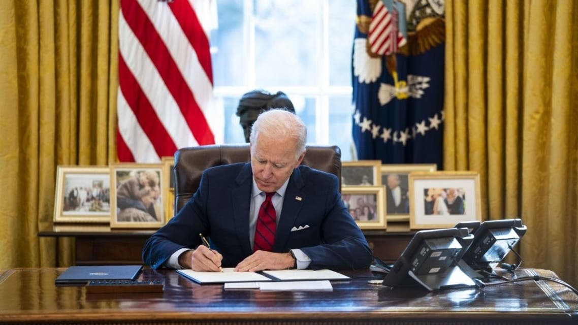 President Joe Biden signs executive actions in the Oval Office of the White House on January 28, 2021 in Washington, DC.  (AFP)