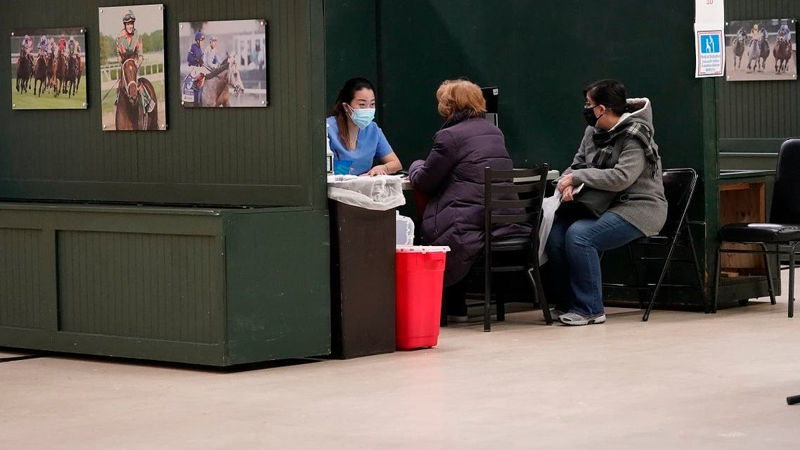 A health care worker, left, prepares to give a coronavirus vaccine to a patient at a COVID-19 vaccination site at the Aqueduct Race Track, Jan. 21, 2021, in the Queens borough of New York. (AP/Mary Altaffer)