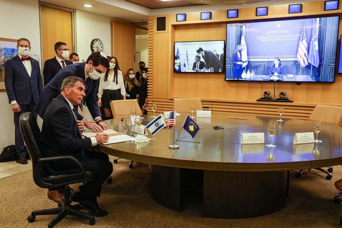 Israel's FM Gabi Ashkenazi (L) signs the joint declaration establishing ties with Kosovo during an official ceremony held over Zoom with his counterpart from Kosovo Meliza Haradinaj Stublla (screen), at the Israeli Foreign Ministry headquarters in Jerusalem on February 1, 2021. (Menahem Kahana/AFP)