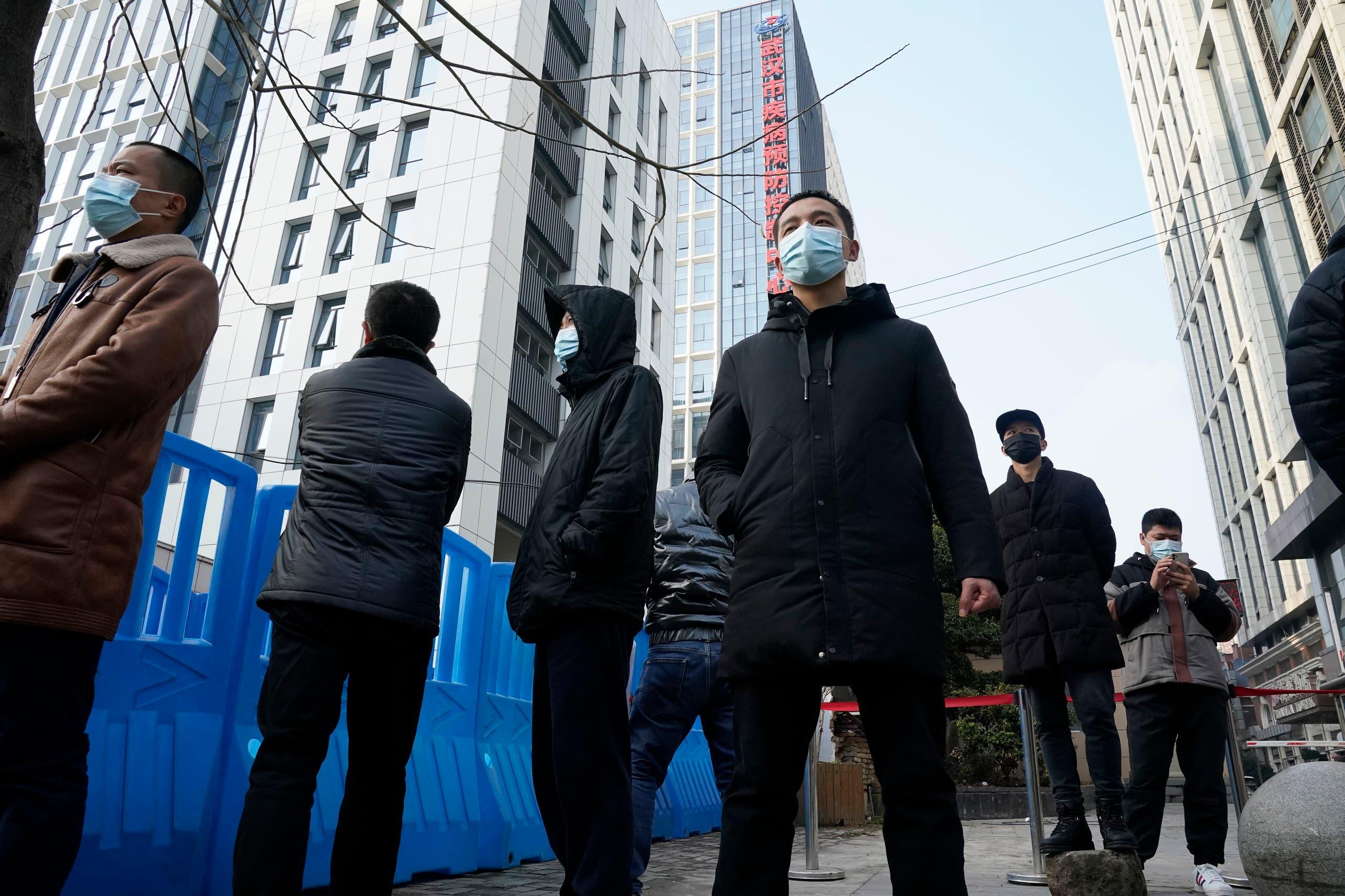 أفراد الأمن في ثياب مدنية خارج مركز ووهان للسيطرة على الأمراض والوقاية منها يوم 1 فبراير 2021