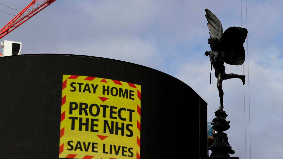 The Eros statue stands in Piccadilly Circus above an NHS sign on the advertising boards in London. (AP)
