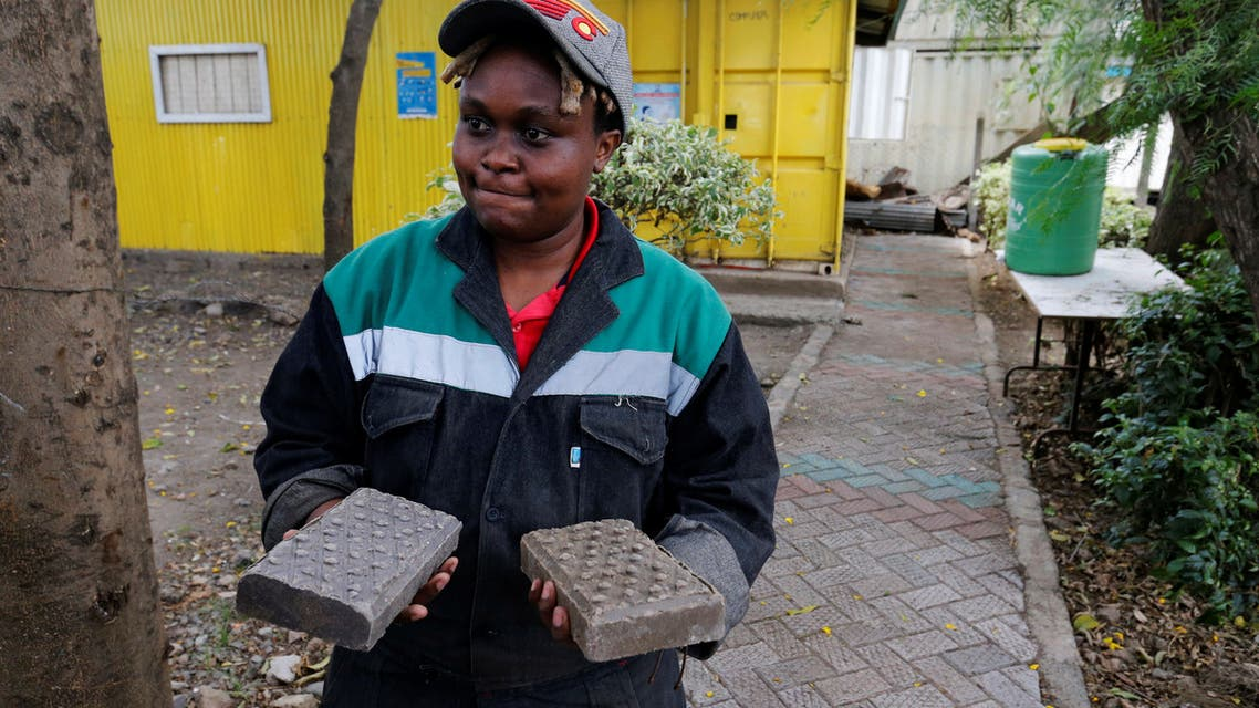 A worker at the Gjenge Makers, a social enterprise that recycles and up-cycles waste plastic into construction products such as paving bricks, arranges mould floor paving in Nairobi, Kenya January 21, 2021. Picture taken January 21, 2021. REUTERS/Thomas Mukoya