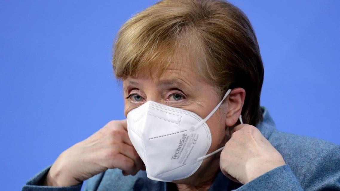 German Chancellor Angela Merkel removes her face mask ahead of a news conference in Berlin, on February 1, 2021. (AFP)