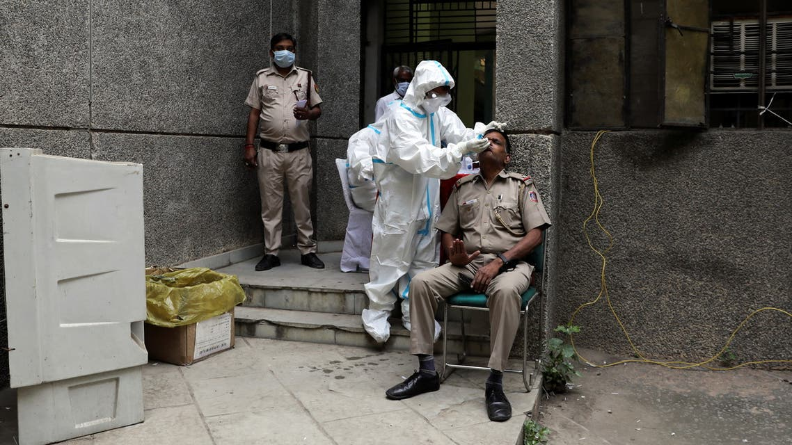 A healthcare worker wearing personal protective equipment (PPE) collects a swab sample from a policeman amidst the spread of the coronavirus disease (COVID-19), at a testing center in New Delhi, India, October 29, 2020. REUTERS/Anushree Fadnavis