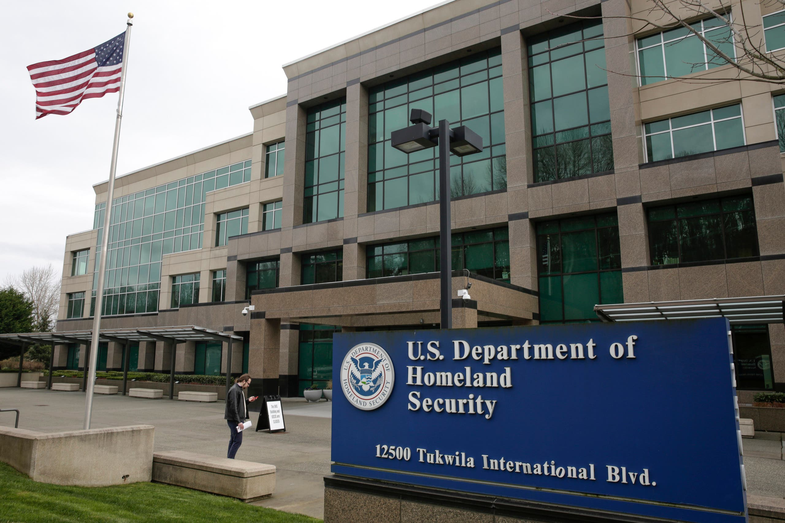A man stands outside the US Department of Homeland Security (DHS) building and US Citizenship and Immigration Services (USCIS). (AFP)