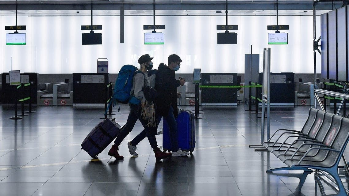 Passengers walk past empty check-in counters at the Terminal 2 of El Prat airport in Barcelona on November 19, 2020. (Pau Barrena/AFP)