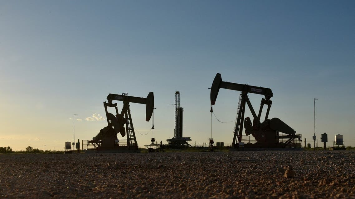 Pump jacks operate in front of a drilling rig in an oil field in Midland, Texas, US. (Reuters)