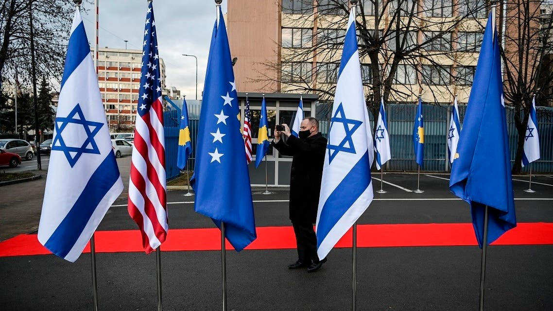 A Kosovo Albanian man takes pictures of Israeli's, US and Kosovo's flag displayed during a ceremony at the headquarters of the Foreign Ministry in Pristina on February 1, 2021. (Armend Nimani/AFP)
