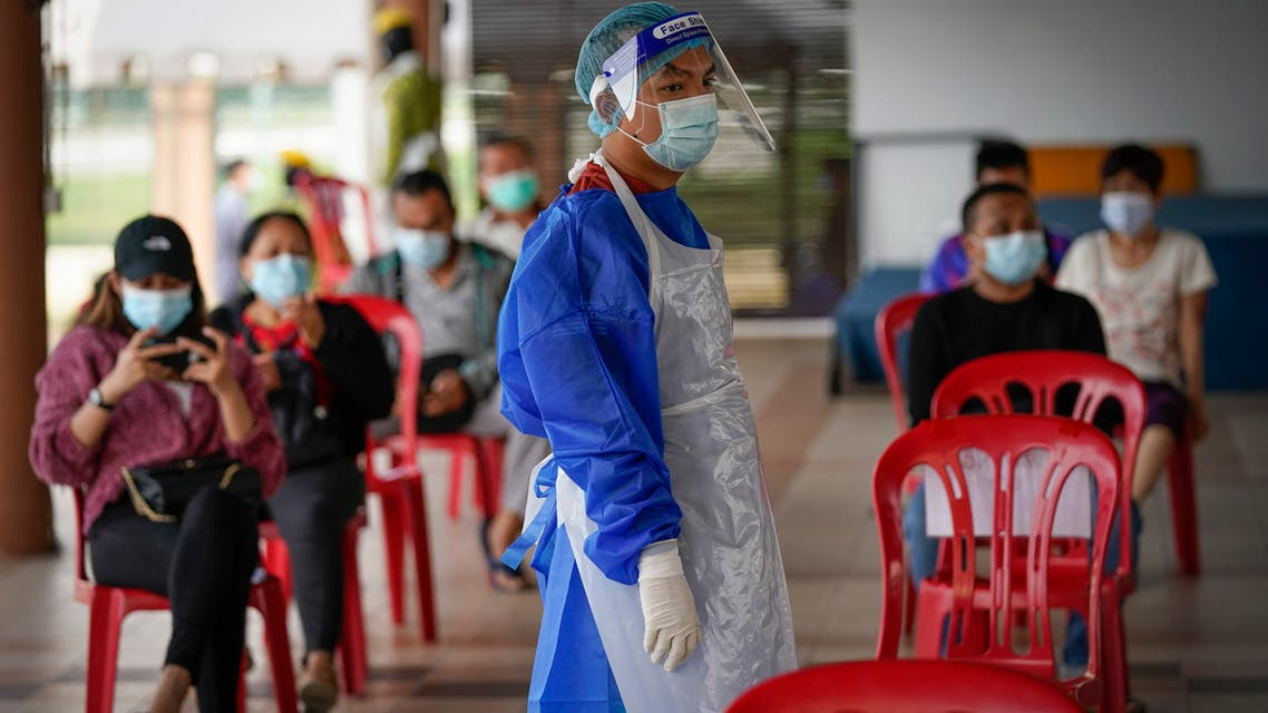A medical worker wearing protective suits stand beside people waiting for their turn for coronavirus testing at a center for private COVID-19 testing in Petaling Jaya, Malaysia, on Monday, Feb. 1, 2021. (AP)