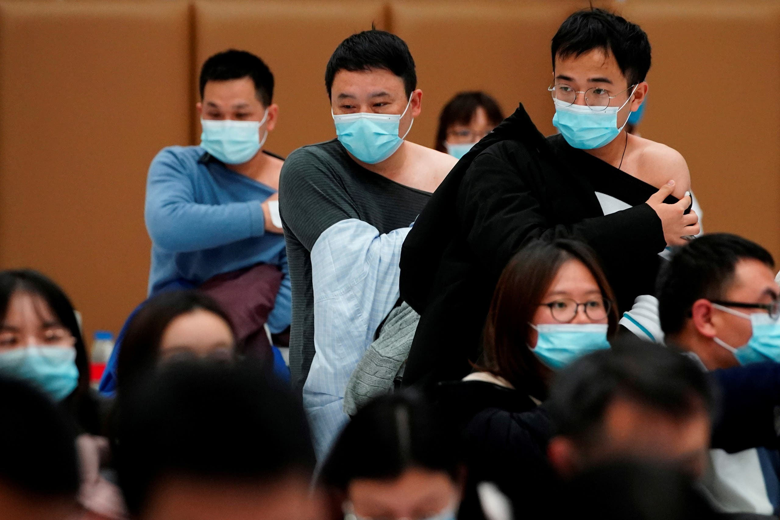 People stand at a vaccination site after receiving a dose of a coronavirus disease (COVID-19) vaccine, in Shanghai. (Reuters)
