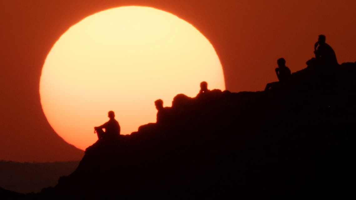 Ethiopian refugees who fled the Ethiopia's Tigray conflict watch the sunset on a hill at the Um Raquba refugee camp in Sudan's eastern Gedaref state on December 12, 2020.