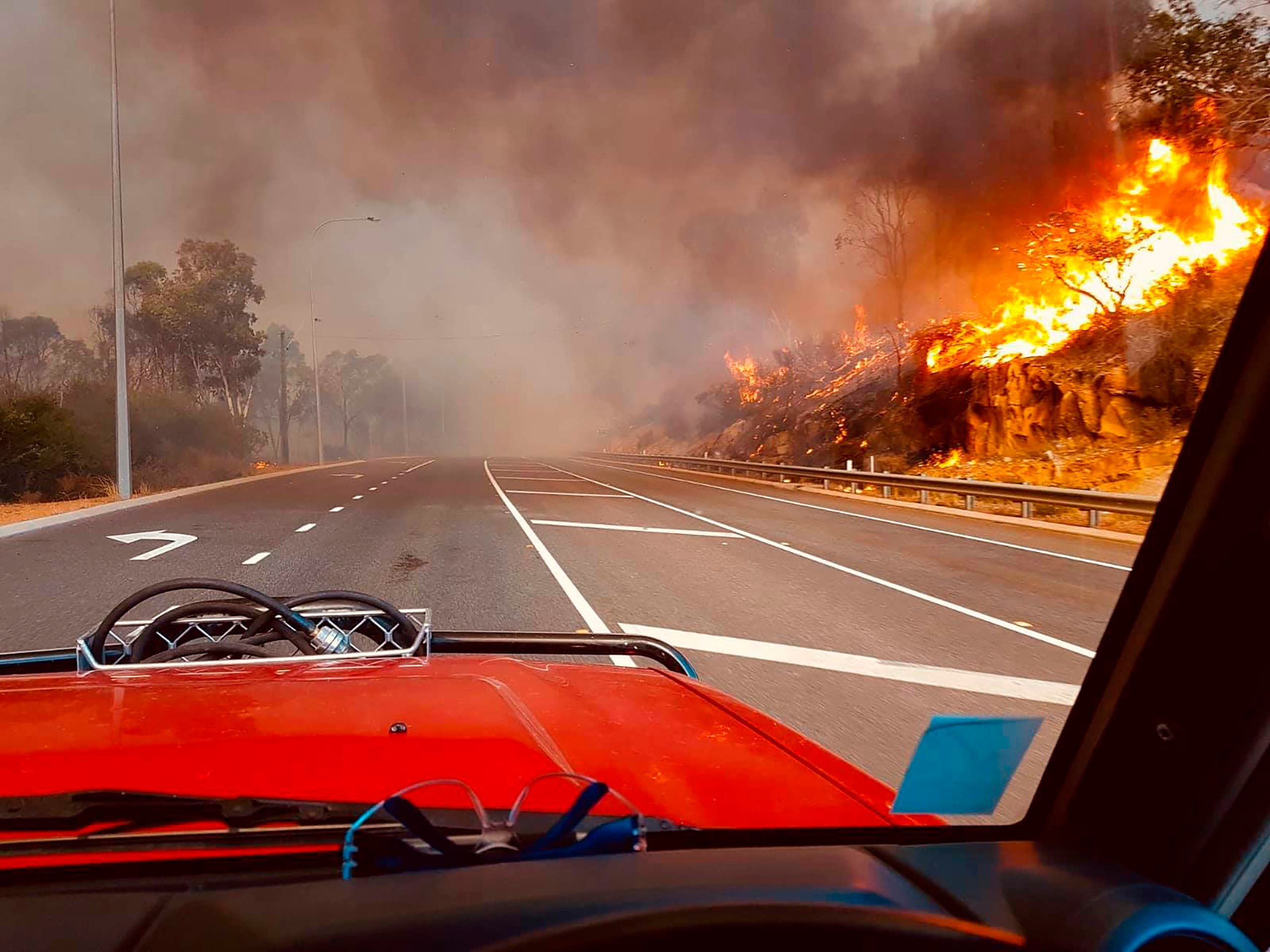 In this photo provided by Department of Fire and Emergency Services, flames approach a road at Wooroloo, near Perth, Australia, Monday, Feb. 1, 2021. (AP)