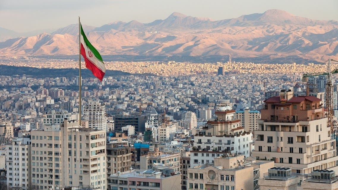 Waving Iran flag above skyline of Tehran at sunset. (iStock)