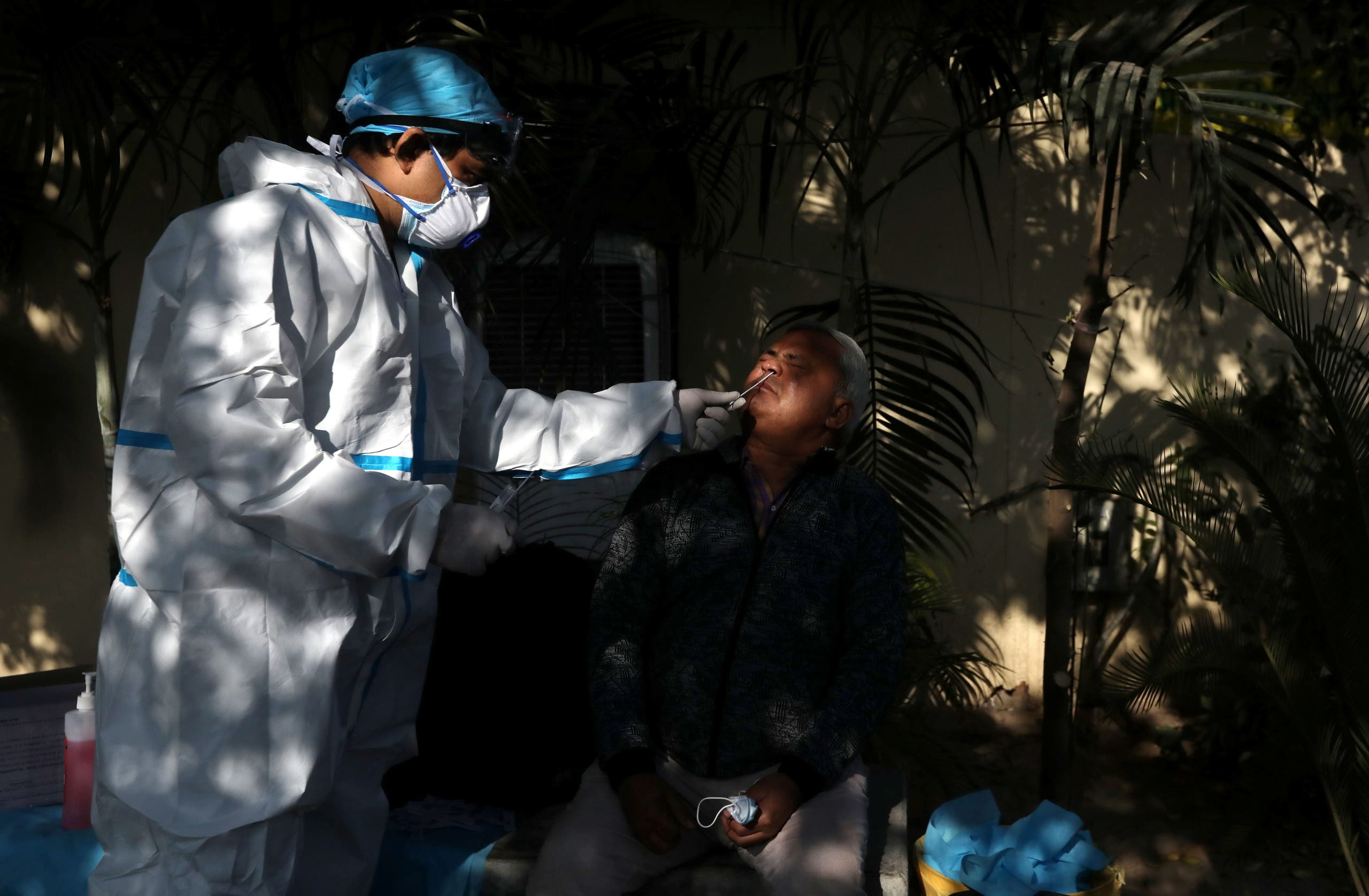 A healthcare worker wearing personal protective equipment (PPE) collects a swab sample from a man amidst the spread of the coronavirus disease (COVID-19), at a bus depot in New Delhi, India, December 14, 2020. (Reuters)