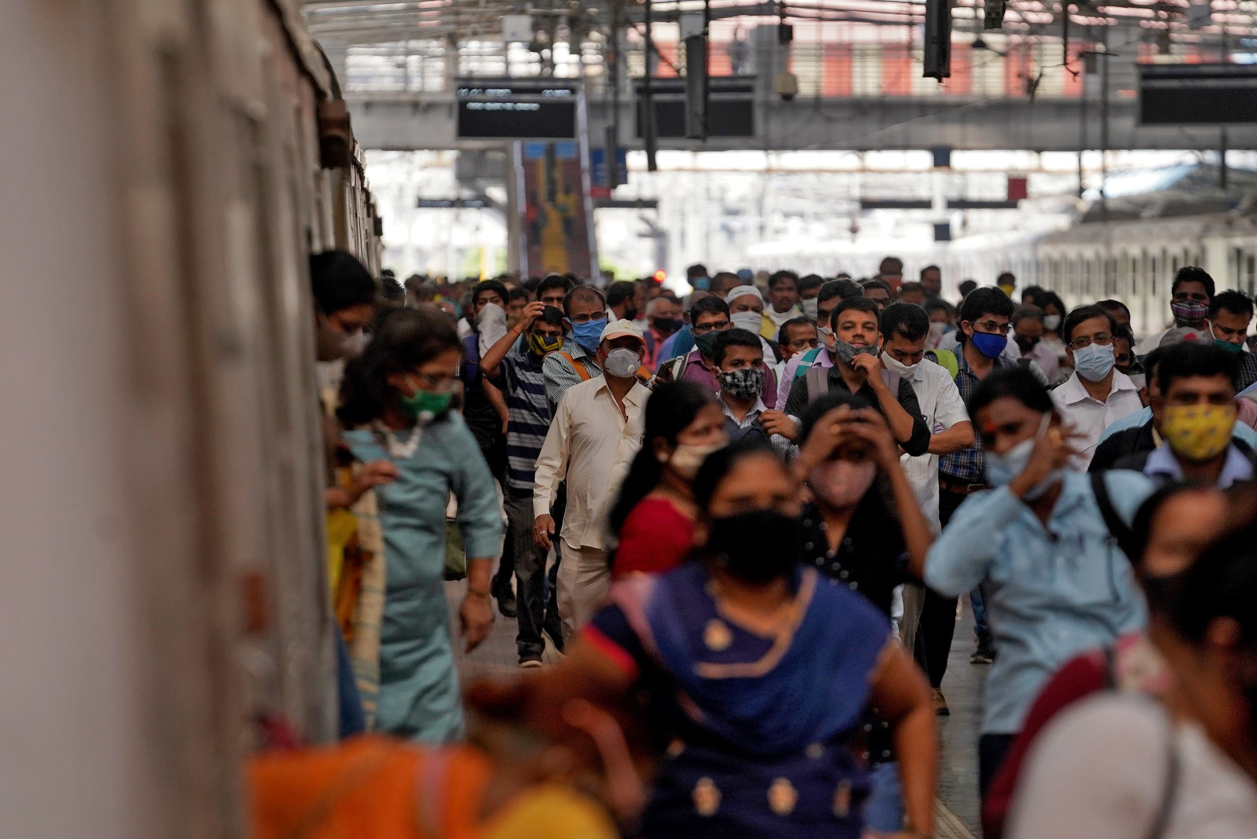 People covering their faces with protective masks disembark a suburban train after authorities resumed the train services for all commuters after it was shut down to prevent the spread of the coronavirus disease (COVID-19), at a railway station in Mumbai, India, February 1, 2021. REUTERS/Hemanshi Kamani