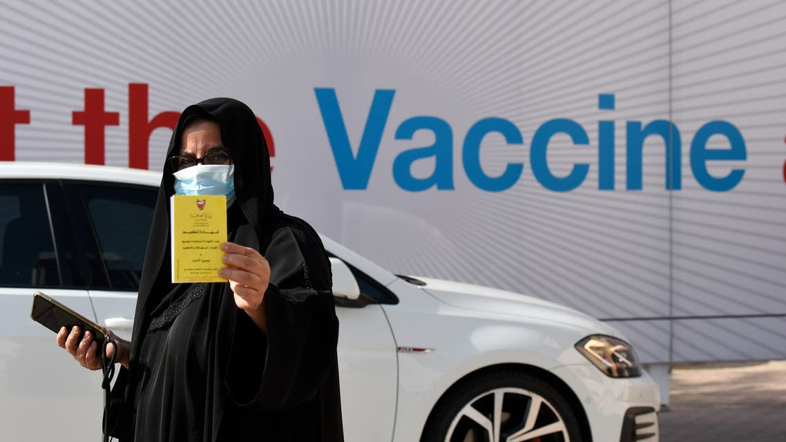 A woman displays her COVID-19 vaccine certificate in front of the Bahrain International Exhibition and Convention Center in the capital Manama, on December 24, 2020. (AFP)