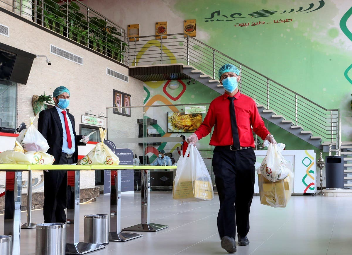 A food delivery worker wearing protective face mask and gloves, following the outbreak of the coronavirus disease (COVID-19), carries Ramadan meal orders at a restaurant in Riyadh, Saudi Arabia April 26, 2020. (Reuters)