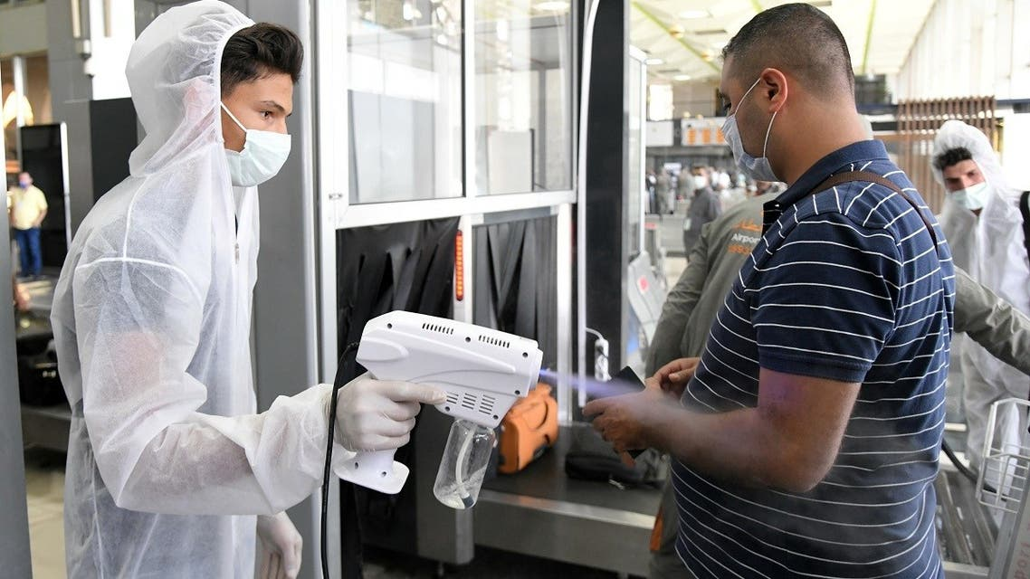 A health worker sprays sanitizer on a passenger at Damascus International Airport on its re-opening day for regular international commercial traffic after months of closure following the coronavirus outbreak on October 1, 2020, Syria. (Reuters)