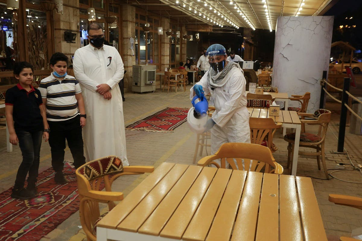 A worker wears a protective suit, following the outbreak of the coronavirus disease (COVID-19), sterilizes the tables before the customers sit down after a restaurant reopened, in Riyadh. (Reuters)
