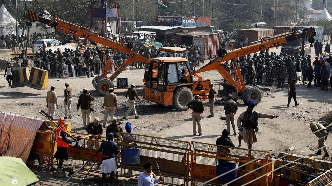 Police officers put barricades with the help of cranes at the site of a protest where farmers are protesting against farm laws, at Singhu border, in New Delhi, India, on January 27, 2021. (Reuters)