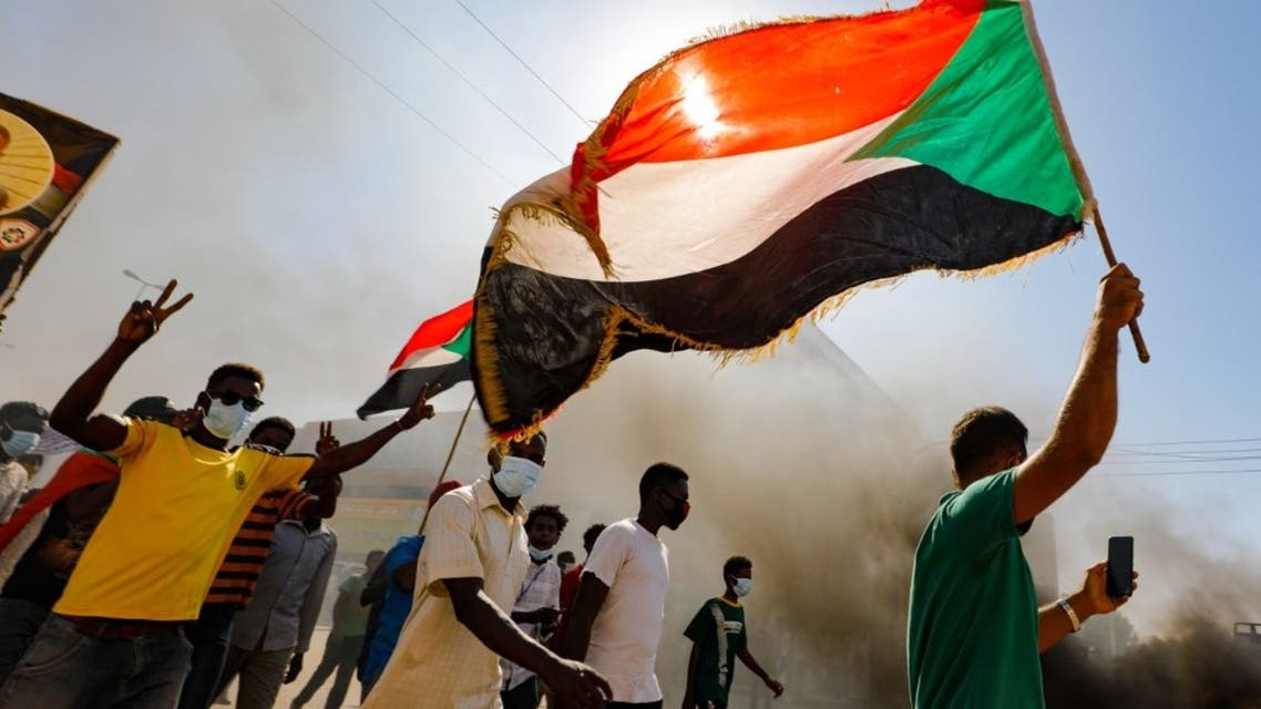 Sudanese youths wave the national flag as they rally in the streets of the capital Khartoum, chanting slogans and burning tires, on December 19, 2020. (AFP)