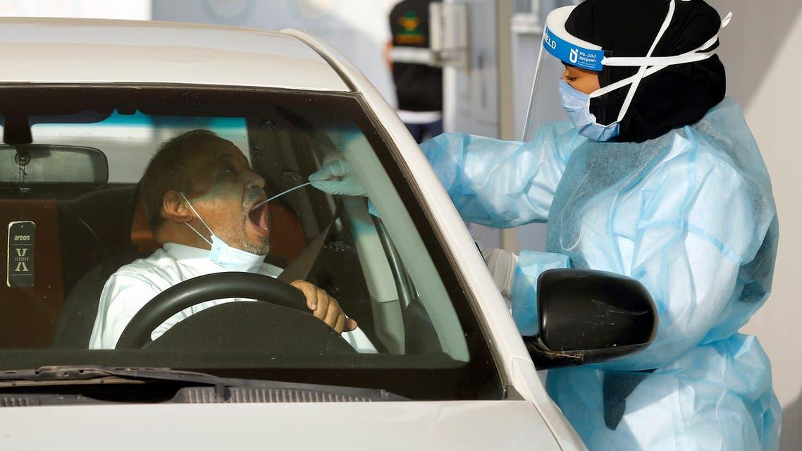 Saudi health worker Wedad Modaifn, collects a swab sample for a polymerase chain reaction (PCR) test at drive-through testing center, at King Abdulaziz University in Jiddah, Saudi Arabia, Wednesday, Feb. 3, 2021. (AP)