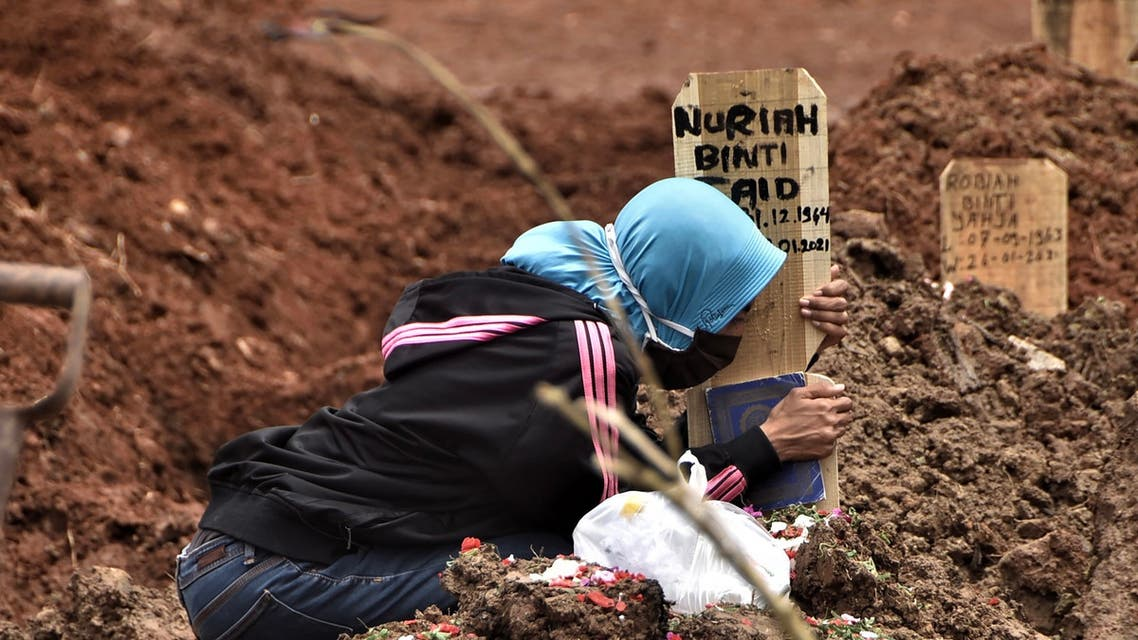 A woman grieves over the grave of a loved one who died of the COVID-19 coronavirus at a cemetery in Bekasi on January 28, 2021, after Indonesia passed more than one million coronavirus cases on January 26. (AFP)