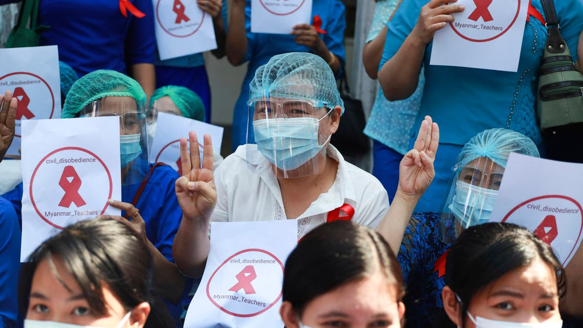 Teachers from the Yangon Education University flash the three-finger protest gesture while holding signs that read: Civil Disobedience Myanmar Teachers Friday, Feb. 5, 2021 in Yangon, Myanmar. (AP)