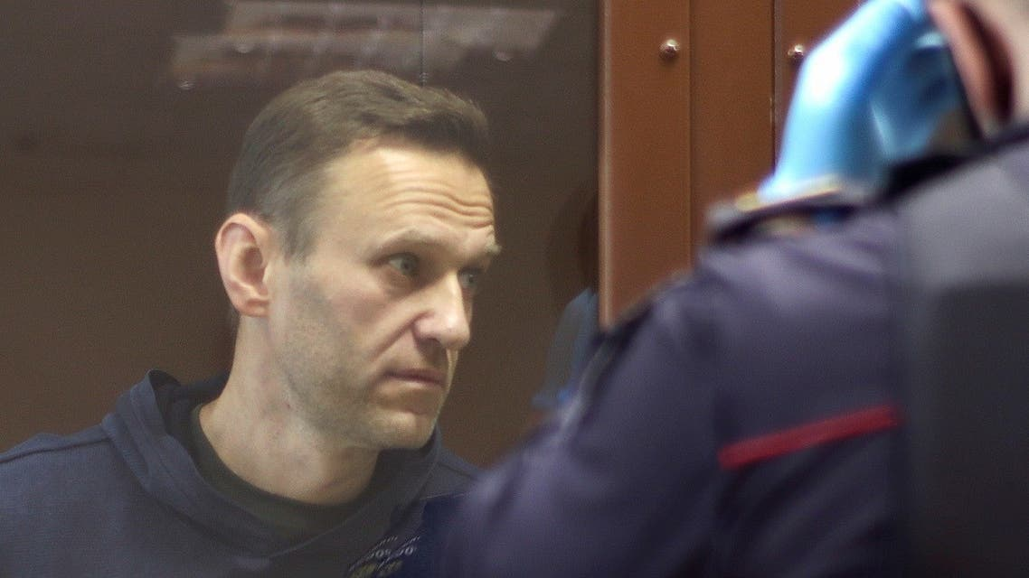 Kremlin critic Alexei Navalny, who is accused of slandering a Russian World War Two veteran, stands inside a defendant dock before a court hearing in Moscow, Russia, on February 5, 2021.  (Reuters)