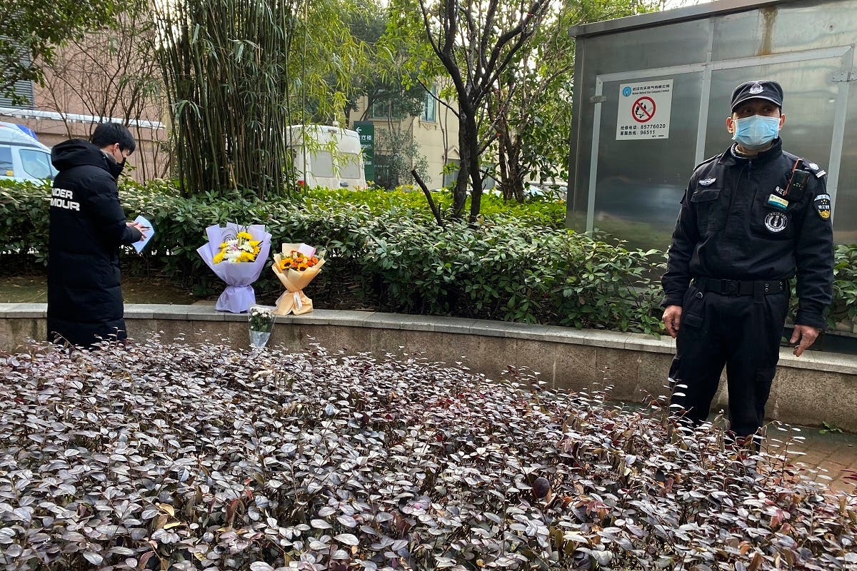 A security guard stands nearby as a man visiting the Wuhan Central Hospital leaves flowers in memory of Li Wenliang, Feb. 7, 2021. (AP/Ng Han Guan)
