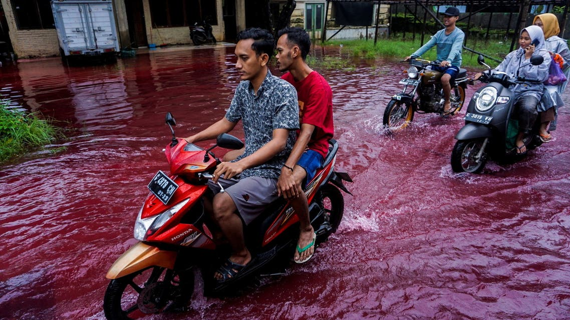 People ride motorbikes through a flooded road with red water due to the dye-waste from cloth factories, in Pekalongan, Central Java province, Indonesia, February 6, 2021. (Reuters)