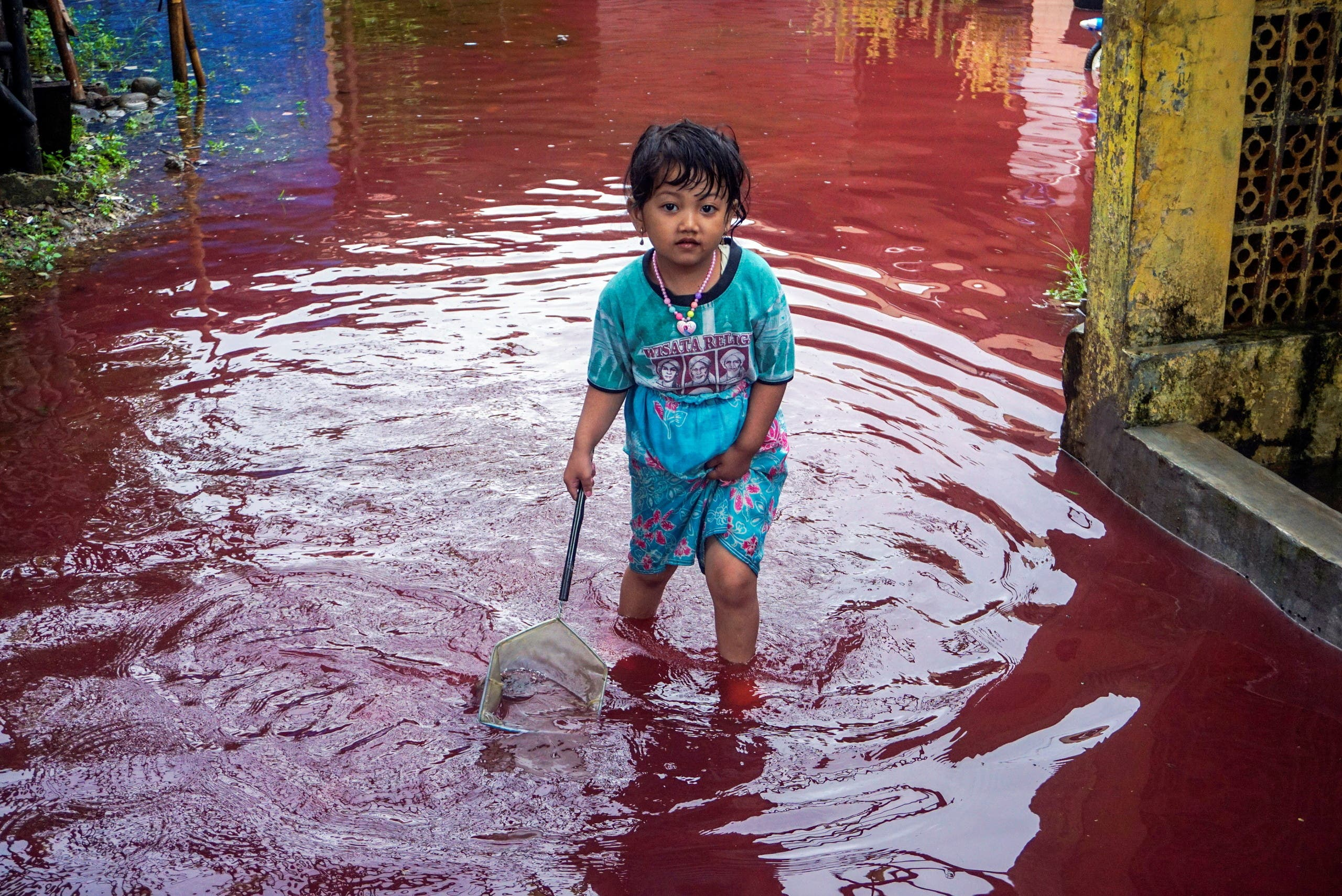 A girl walks through a flooded road with red water due to the dye-waste from cloth factories, in Pekalongan, Central Java province, Indonesia, February 6, 2021. (Reuters)