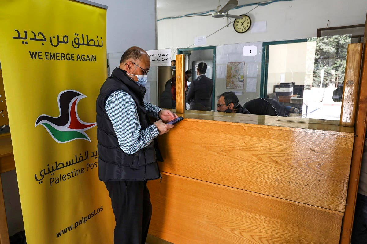 A man is assisted at a post office in the city of al-Bireh, about 15 kilometers north of Jerusalem in the occupied West Bank, on February 7, 2021. (Abbas Momani/AFP)