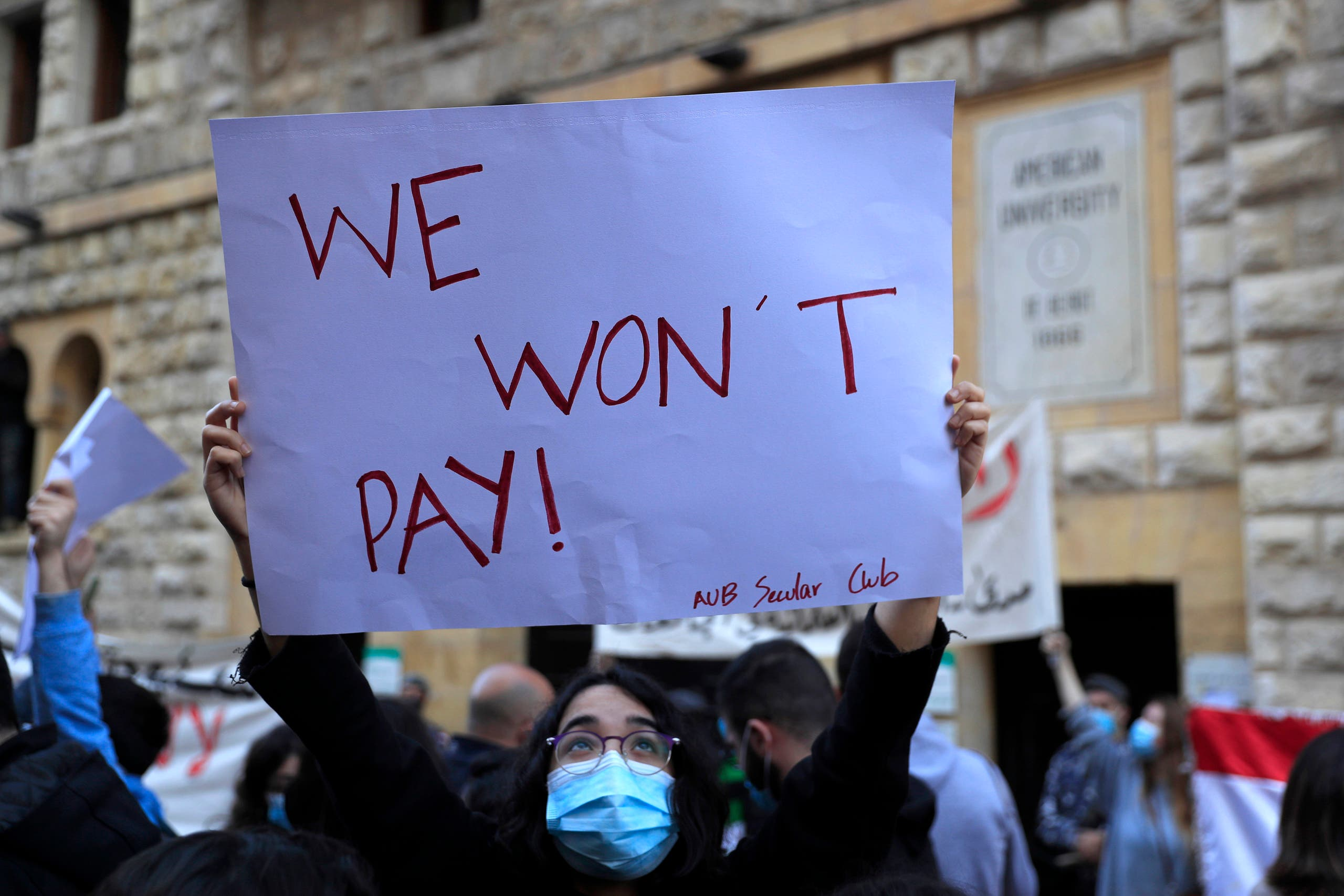 A student from the American University of Beirut (AUB) holds up a placard during a protest against the adjustment of the dollar rate for new tuition fees, in Beirut, Lebanon, Tuesday, Dec. 29, 2020. (File photo: AP)