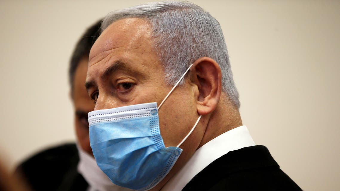 Israeli Prime Minister Benjamin Netanyahu, wearing a face mask, looks on while standing inside the court room as his corruption trial opens at the Jerusalem District Court. (Reuters)
