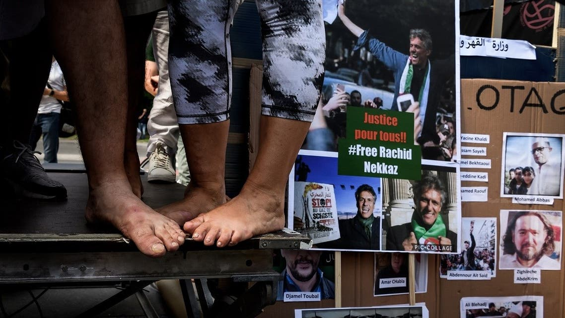 Activists close to the Hirak Algerian protest movement stand barefoot next to photos of prisonners during a demonstration in front of the United Nations Offices in Geneva against the arbitrary arrests in Algeria. (File photo: AFP)