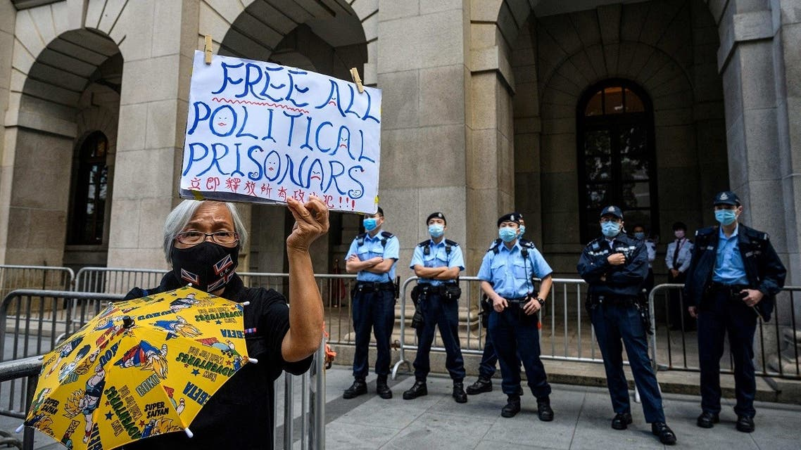 A pro-democracy activist (L) holds up a placard as police stand guard outside the Court of Final Appeal in Hong Kong on February 1, 2021, during a bail hearing for detained media tycoon Jimmy Lai. (Anthony Wallace/AFP)