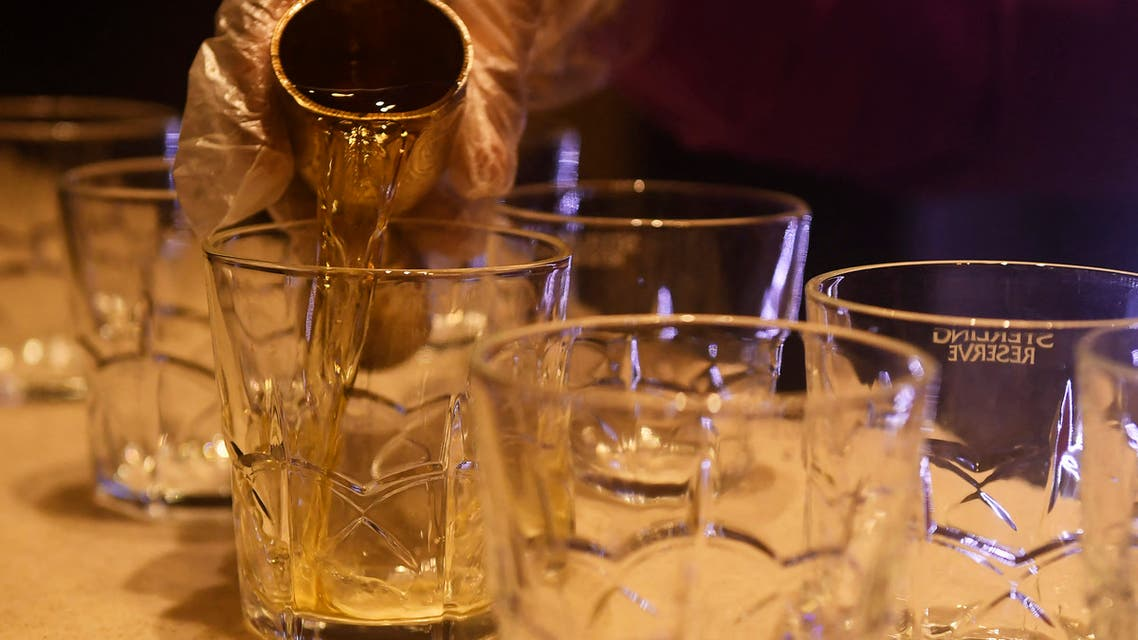 A bartender makes drinks for customers inside a bar. (AFP)