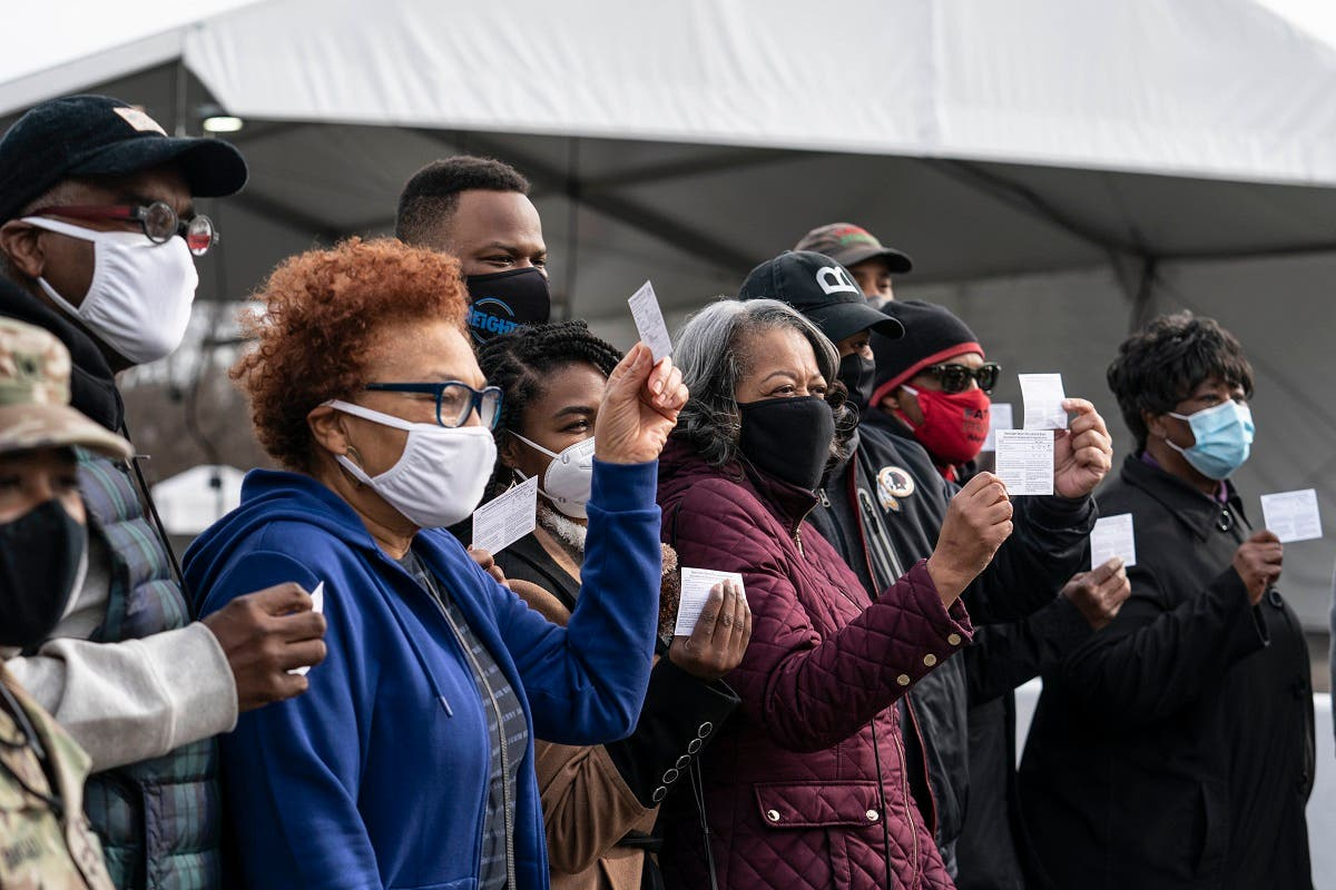 A group of people show off their coronavirus vaccine record cards in the parking lot of Six Flags on February 6, 2021 in Bowie, Maryland, US. (AFP)