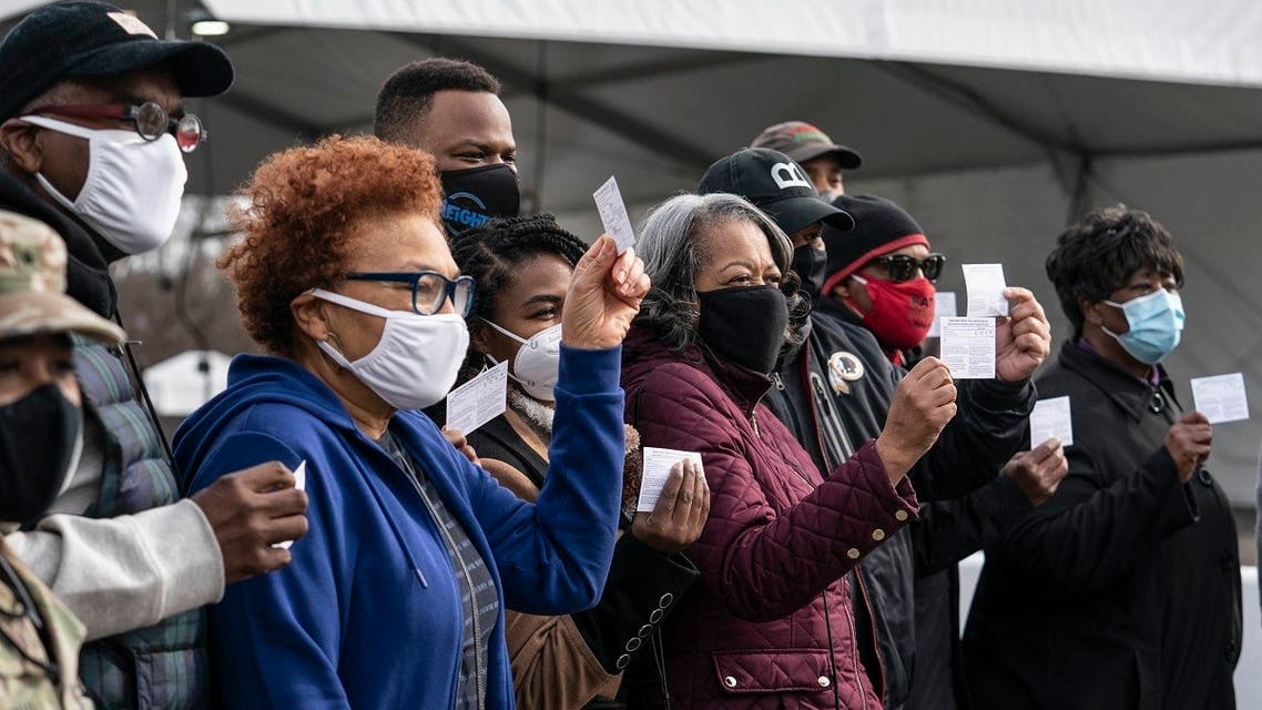 A group of people show off their coronavirus vaccine record cards in the parking lot of Six Flags on February 6, 2021 in Bowie, Maryland. (AFP)