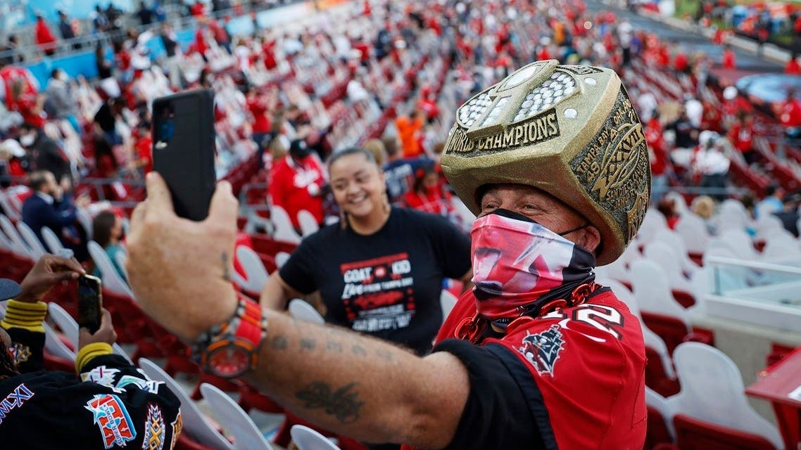 A fan wearing a protective face mask due to the coronavirus disease (COVID-19) takes a selfie inside the stadium before the game. (Reuters)