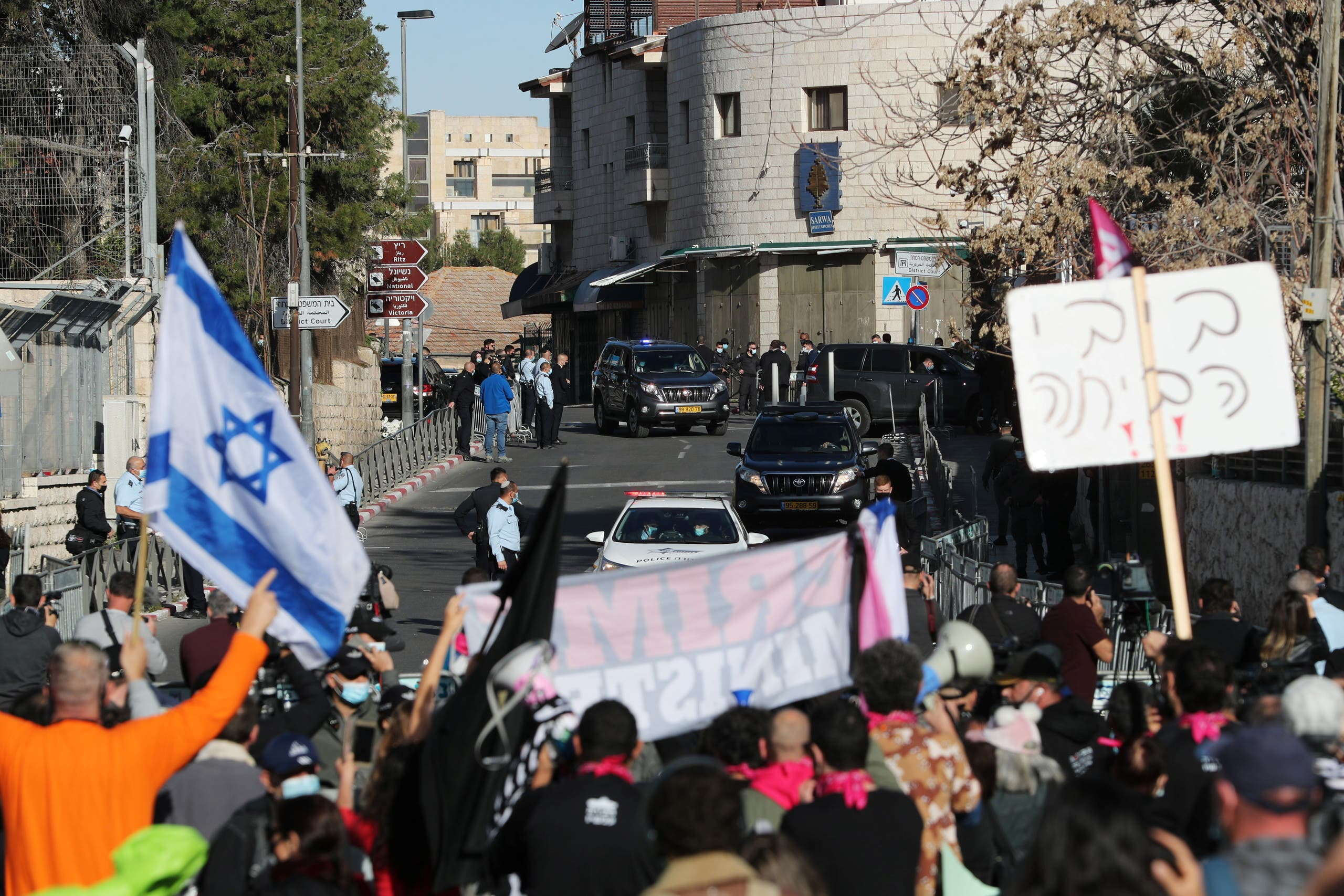 Protesters hold placards and an Israeli flag as a convoy transporting Israeli Prime Minister Benjamin Netanyahu to the District Court arrives ahead of a hearing in his corruption trial in Jerusalem. (Reuters)