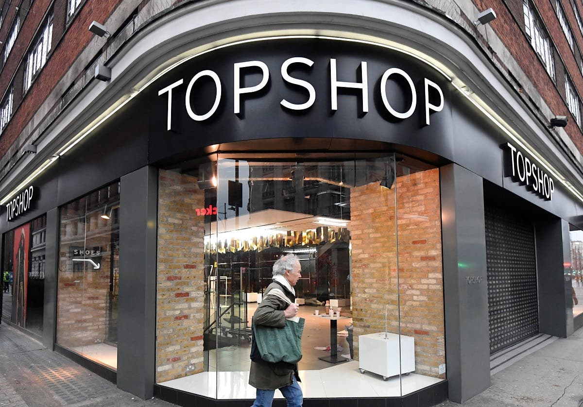 A man walks past a closed branch of Topshop, after the British online fashion retailer ASOS said it has bought the brand amongst others from the collapsed Arcadia group, Londonon February 1, 2021. (Reuters)