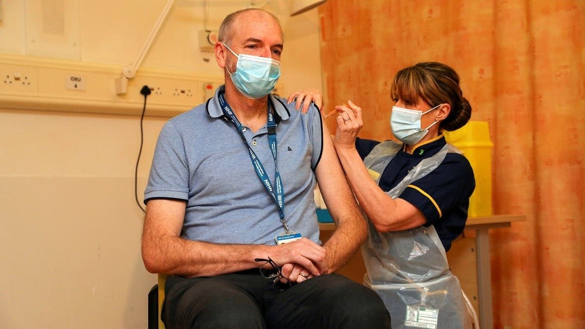 Professor Andrew Pollard, Director of the Oxford Vaccine Group (OVG), and a professor of Paediatric Infection and Immunity receives the Oxford University/AstraZeneca COVID-19 vaccine from nurse Sam Foster at the Churchill Hospital in Oxford, Britain, on January 4, 2021. (Reuters)