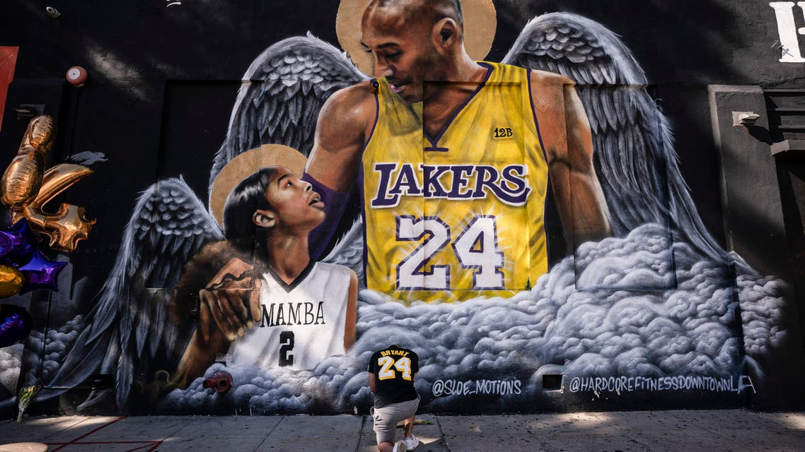 Adam Dergazarian, bottom center, pays his respect for Kobe Bryant and his daughter, Gianna, in front of a mural painted by artist Louie Sloe Palsino, Tuesday, Jan. 26, 2021, in Los Angeles. (AP)