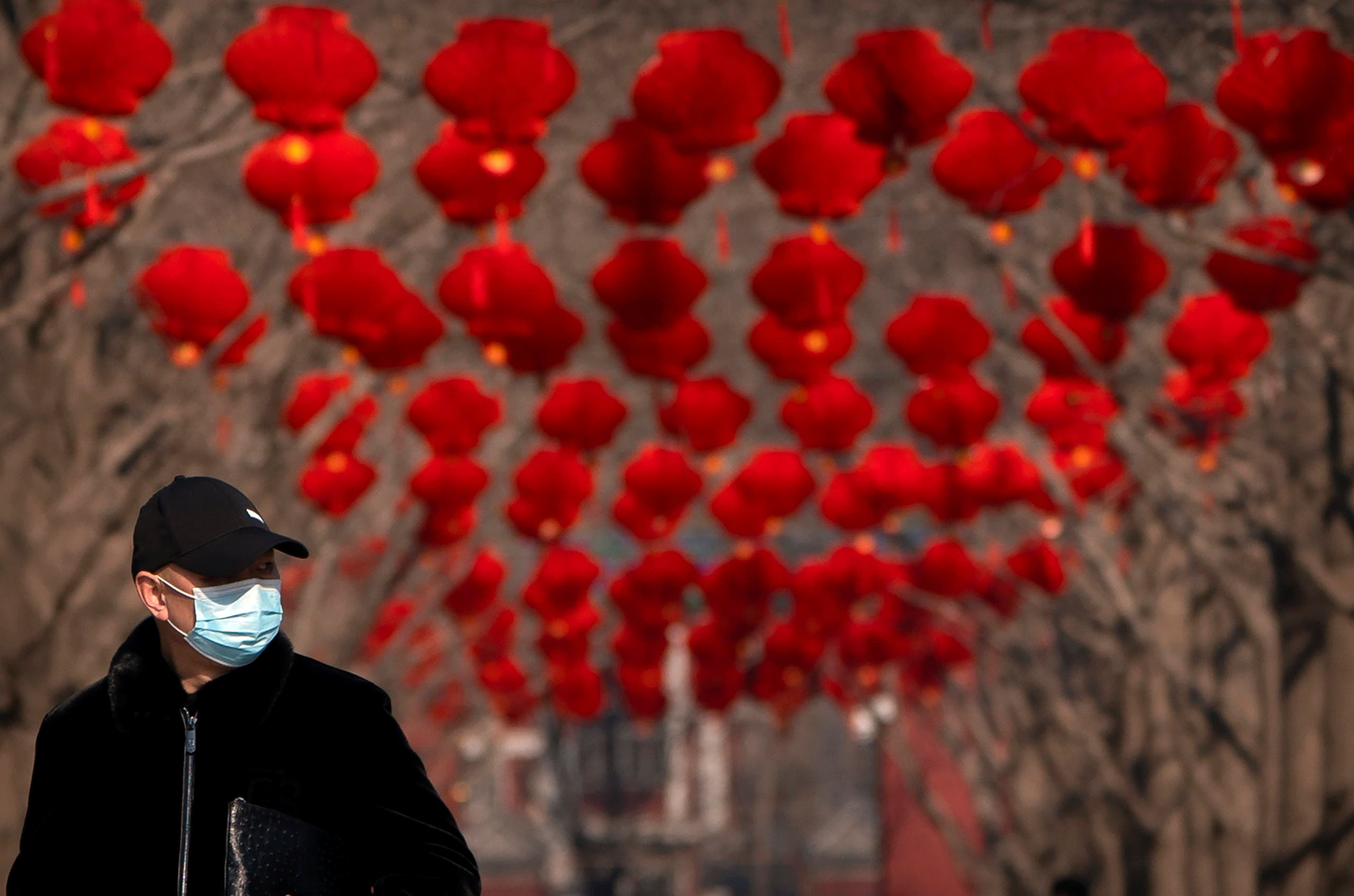 A man wearing a face mask to protect against the spread of the coronavirus walks past rows of decorative lanterns at Ditan Park in Beijing, Tuesday, Feb. 9, 2021. (AP)